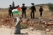 A demonstrator holds a Palestinian flag in front of Israeli forces during a protest in the occupied West Bank in June last year [Mohamad Torokman/Reuters]