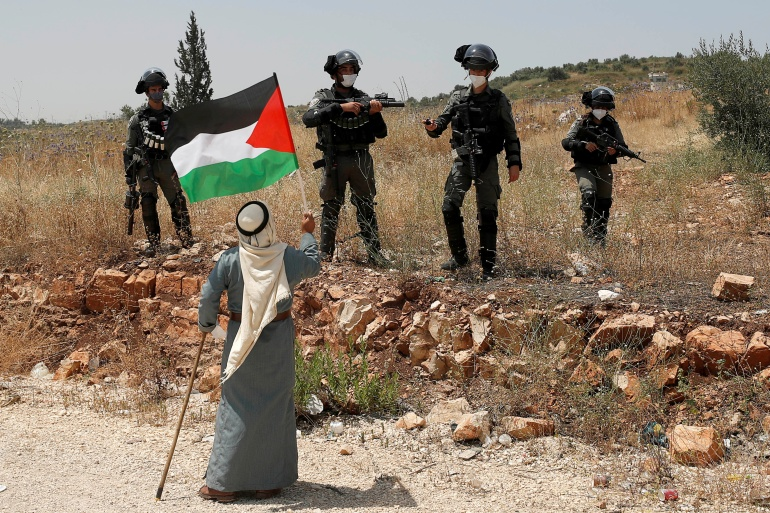 A demonstrator holds a Palestinian flag in front of Israeli forces during a protest against Israel's plan to annex parts of the occupied West Bank, near Tulkarm June 5, 2020 [Mohamad Torokman/Reuters]