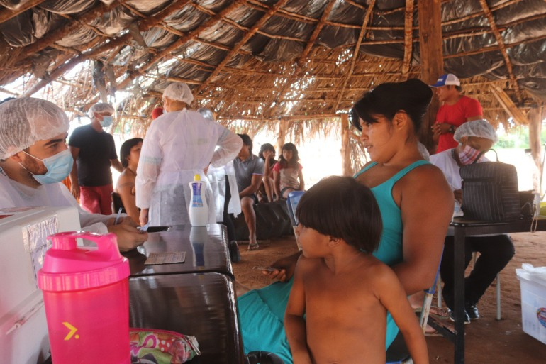 Tuira Yawalapiti and her son prepare to receive the CoronaVac vaccine in the Upper Xingu Reserve, on the margins of the Tuatuari river, Mato Grosso, Brazil [Courtesy of Walamatiu Yawalapiti]