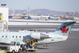 Workers remove luggage from an Air Canada plane on the tarmac at Montreal-Pierre Elliott Trudeau International Airport (YUL) in Montreal, Quebec [File: Bloomberg]