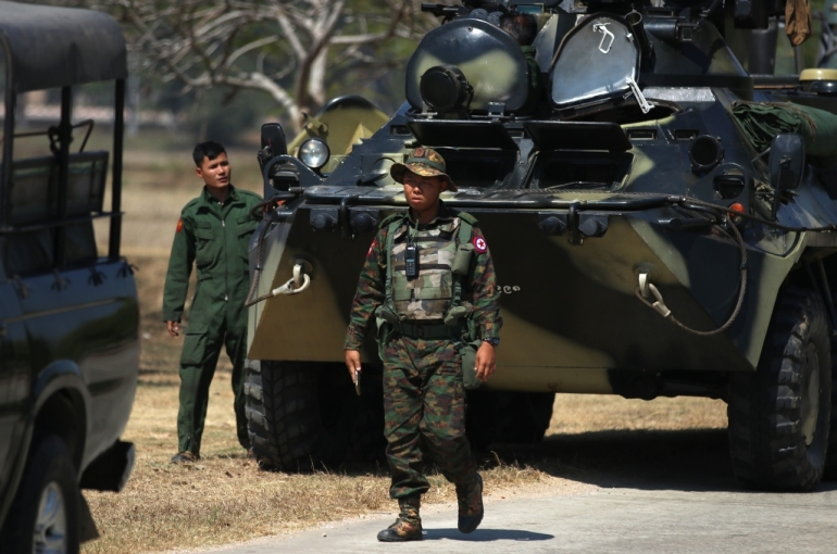 Military vehicles and soldiers stand guard on a road in Naypyidaw. [Maung Lonlan/EPA]