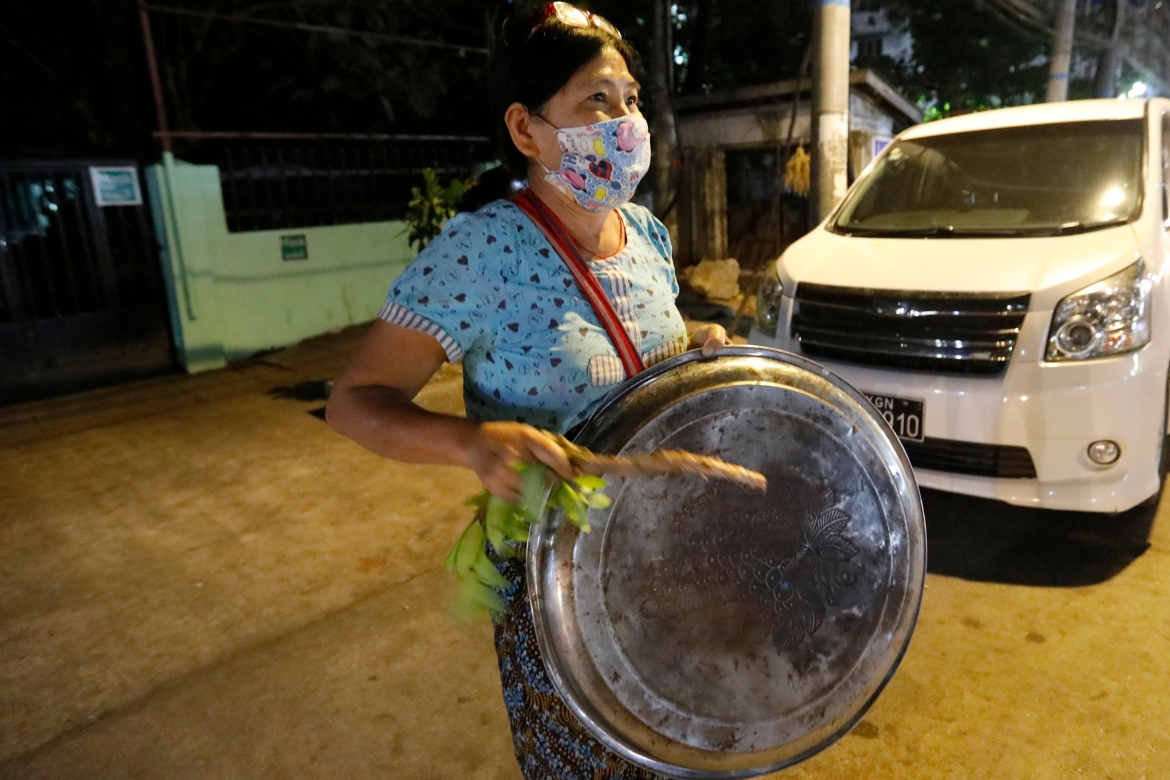 A woman hits a metallic tray as she protests against the military coup, in Yangon. [Nyein Chan Naing/EPA]