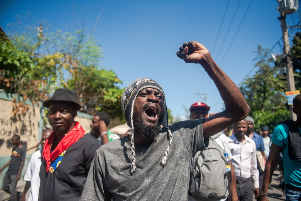 Protesters march on a street in Port-au-Prince. The opposition is demanding Moise leaves power immediately, accusing him of acting like an authoritarian leader and violating the constitution. [Jean Marc Herve Abelard/EPA]