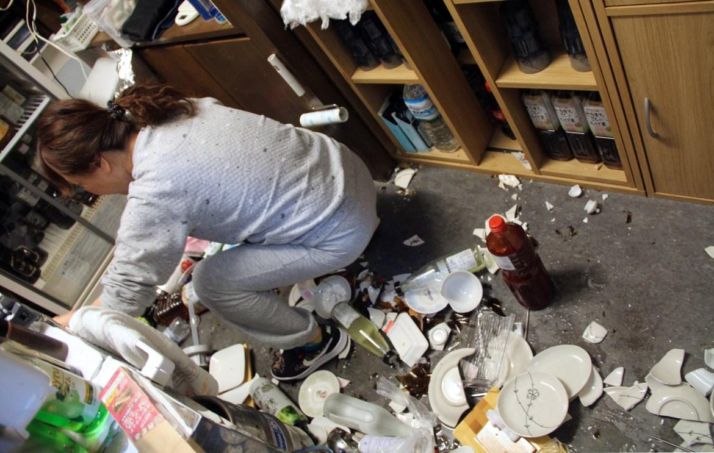 Seorang wanita membersihkan piring pecah di sebuah restoran setelah gempa bumi.  Gempa tersebut menghasilkan getaran kuat di sepanjang bagian pantai timur Jepang, dan terasa kuat di Tokyo, tetapi tidak memicu peringatan tsunami.  [Jiji Press melalui EPA]
