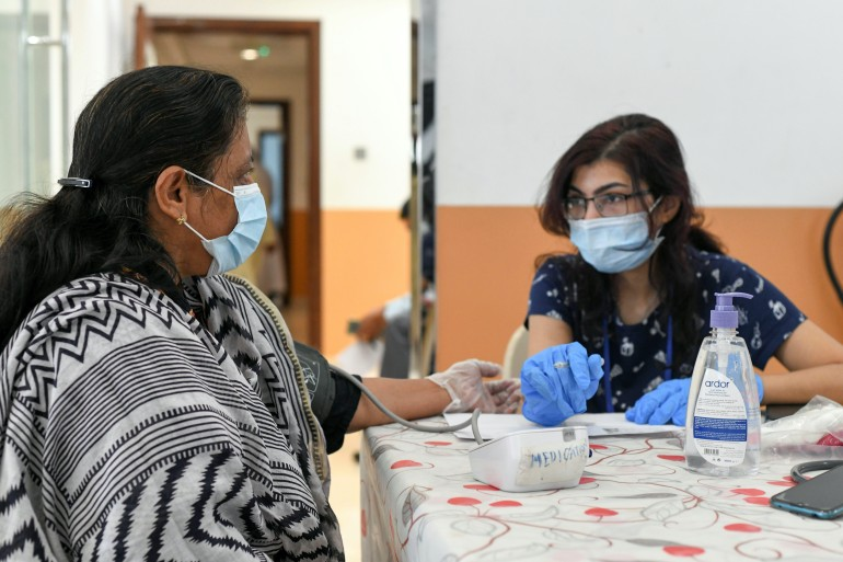 A woman gets tested before receiving a dose of a vaccine against the coronavirus at St Paul's Church in Abu Dhabi, the United Arab Emirates, whose economy the International Monetary Fund forecasts will grow by 3.1 percent this year [File: Khushnum Bhandari/Reuters]