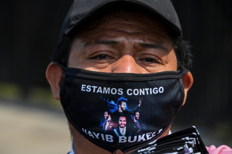 A street vendor wears a face mask with a message of support for Salvadoran President Nayib Bukele, in San Salvador on May 1, 2020 [File: Yuri Cortez/AFP]