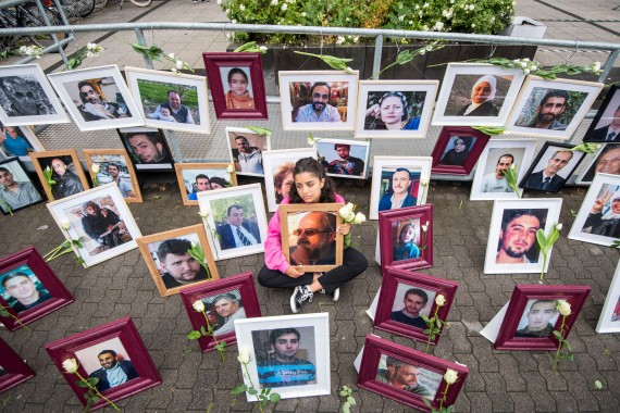 Syrian campaigner Wafa Mustafa sits between pictures of victims of the Syrian government, holding a picture of her father, outside the trial of two former Syrian intelligence officers accused of crimes against humanity, in Germany, in June 2020 [File: Thomas Lohnes/AFP]