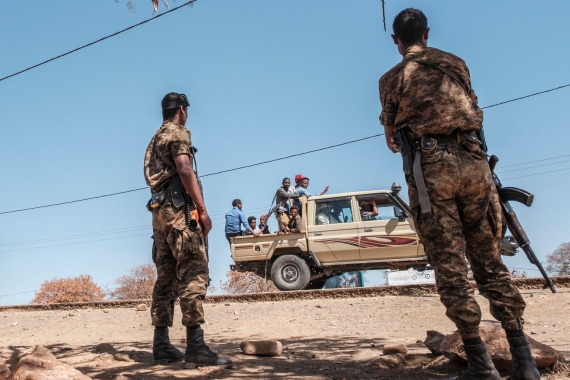 Ethiopian soldiers watch as a pick-up truck with militiamen passes by at the Mai Aini refugee camp in Ethiopia [File: Eduardo Soteras/AFP]