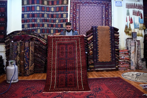 Abdul Wahab, one of Kabul's top tribal carpet collectors, displays a rug inside his shop on Chicken Street in the capital. [Wakil Kohsar/AFP]