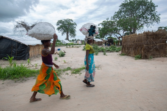 Women carry bags of charcoal at a centre for internally displaced persons in the Tara Tara district of Matuge, northern Mozambique on February 24, 2021 [File: AFP/Alfredo Zuniga]