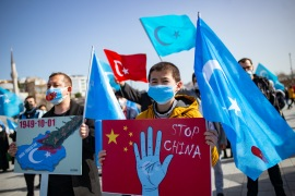 Members of the Muslim Uighur minority hold placards as they demonstrate at Uskudar Square in Istanbul on February 26, 2021 (AFP/Yasin Akgul) (AFP)