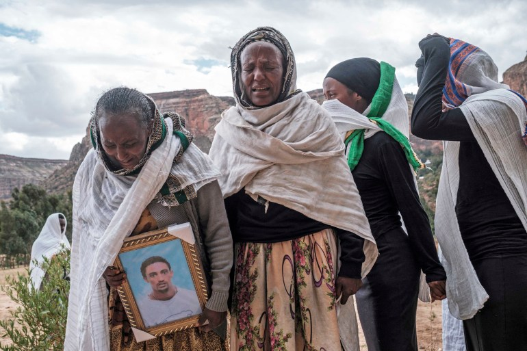 People gather to mourn the victims of a massacre allegedly perpetrated by Eritrean soldiers in the village of Dengolat in the Tigray region of Ethiopia on February 26, 2021 [File: AFP/Eduardo Soteras]