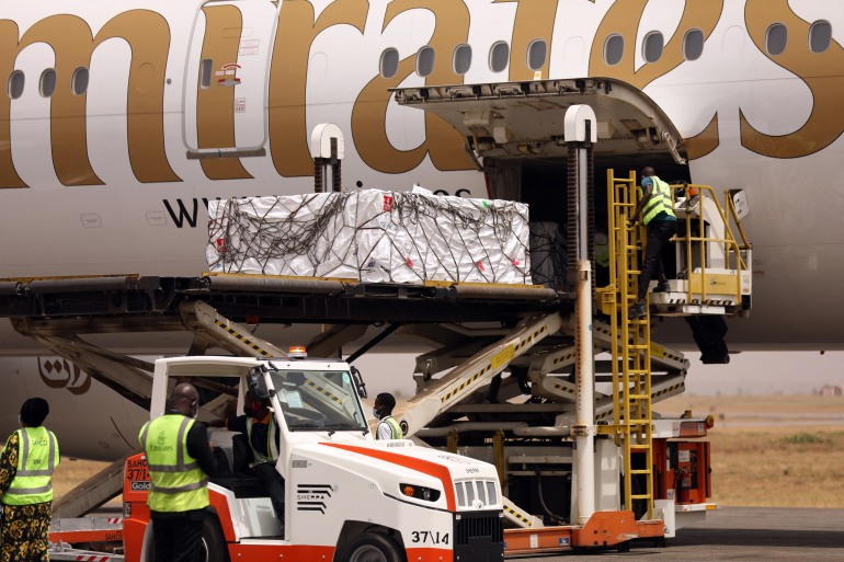 The first batch of Oxford/AstraZeneca COVID-19 vaccine doses are offloaded from a plane during its arrival at the Nnamdi Azikiwe International Airport, in Abuja, Nigeria on March 2, 2021 [Kola Sulaimon/AFP]