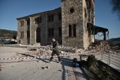 A man walks past a heavily damaged church in the village of Mesochori after a 6.3-magnitude earthquake hit Greece's central region on Wednesday [Sakis Mitrolidis/AFP]