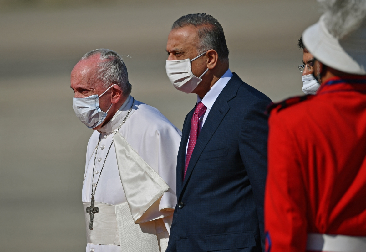 Pope Francis walks alongside Iraq's Prime Minister Mustafa al-Kadhem upon his arrival in Baghdad. [Vincenzo Pinto/AFP]