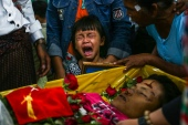 The daughter of Zwee Htet Soe, a protester who died during a demonstration against the military coup on March 3, cries during her father's funeral in Yangon on Friday [Stringer/AFP]