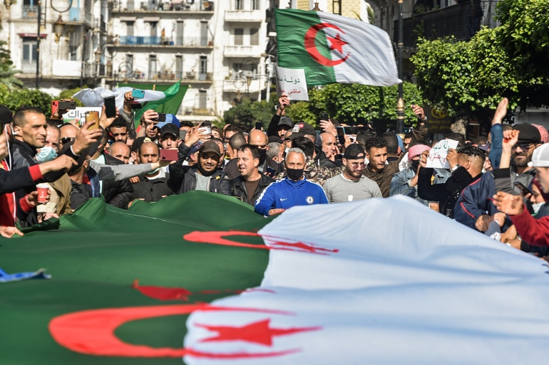 Algerians wave national flags during an anti-government protest in the capital Algiers on March 5 [Ryad Kramdi/AFP]