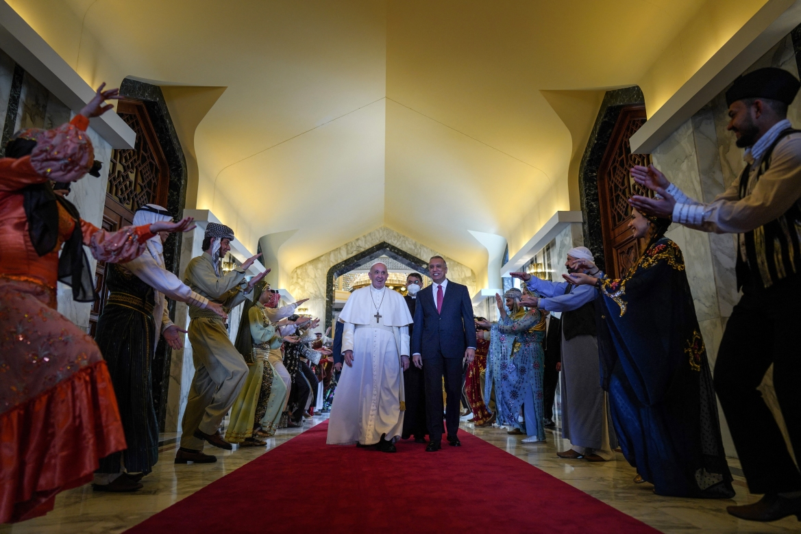 The pope landed in war-battered Iraq on the first-ever papal visit, defying security fears and the pandemic to visit one of the world's oldest and most persecuted Christian communities. [Ayman Henna/AFP]
