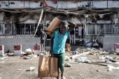 A young boy holds grocery bags as he walks away from a burned down and looted Auchan supermarket in the upmarket area of Almadies in Dakar on Saturday [John Wessels/AFP]