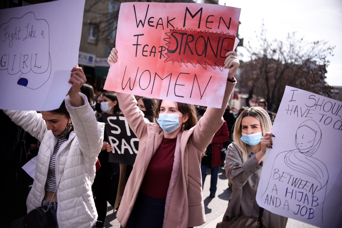 Women hold placards and shout slogans during a rally for gender equality and against violence towards women to mark the International Women's Day in Pristina, Kosovo. [Armend Nimani/AFP]
