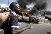 A protester runs past a burning car during protests in Dakar [John Wessels/AFP]