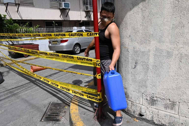 A Manila resident at a street entrance ahead of a lockdown in the Philippine capital as the number of new daily cases soars past 5,000 [Ted Aljibe/AFP]
