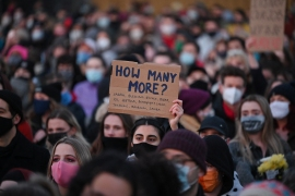 Well-wishers, one with a placard that reads 'How many more', gather at the band-stand where a planned vigil in honour of alleged murder victim Sarah Everard which was officially cancelled due to COVID-19 restrictions, was to place on Clapham Common, south London, March 13, 2021 [Justin Tallis/AFP]