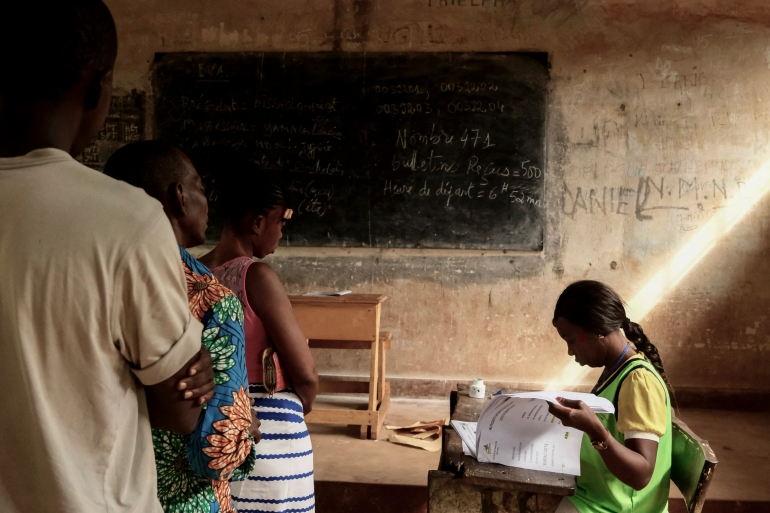 People wait as an electoral commission official checks a voter's roll at a polling station in Bangui [Camille Laffont/AFP]