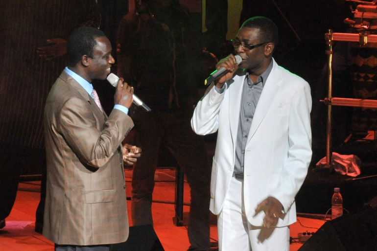 In this file photo taken on September 9, 2012 Senegalese singer and Culture Minister Youssou Ndour (R) and Senegalese singer Thione Seck (L) perform at a relief concert for flood victims at Dakar's Grand Theatre [File: Seyllou/AFP]
