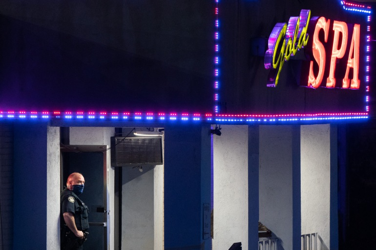 A police officer stands outside a massage parlour where three people were shot and killed on March 16, 2021, in Atlanta, Georgia [Elijah Nouvelage/AFP]