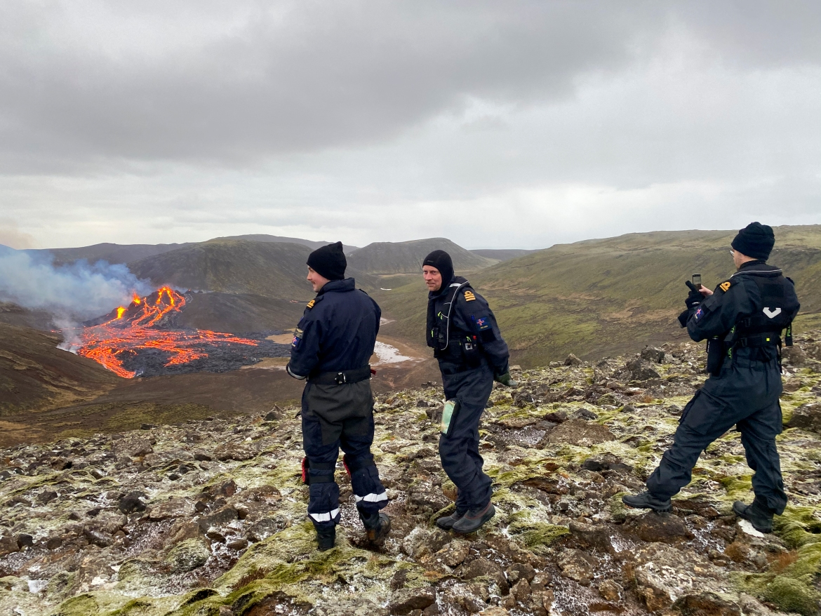 Icelandic coastguard members inspect the lava flowing from the erupting Fagradalsfjall volcano west of the capital, Reykjavik. [Handout/Icelandic Coast Guard via AFP]