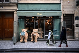 A woman walks in front of teddy bears displayed on the terrace of a closed restaurant in Paris on the first day of a new lockdown [Anne-Christine Poijoulat/AFP]