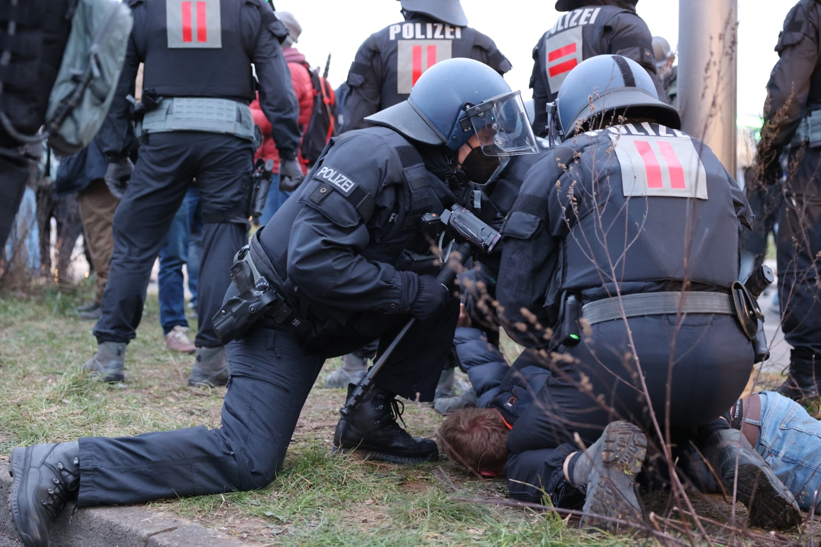 Police officers in riot gear hold down a protester during a demonstration demanding an end to COVID restrictions in the central German city of Kassel. [Yann Schreiber/AFP]