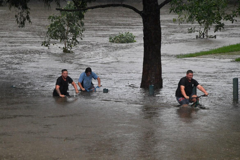 As pessoas andam de bicicleta por um parque inundado nas margens do rio Nepean, no subúrbio de Penrith, enquanto Sydney se preparava para a pior enchente em décadas.  [Saeed Khan / AFP]