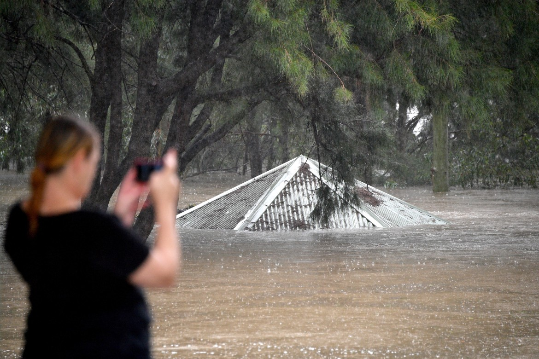 Uma mulher tira fotos de um parque inundado ao longo do transbordante rio Nepean em Penrith, Sydney.  [Saeed Khan / AFP]