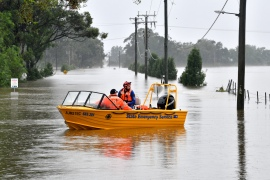 Members of State Emergency Service load medical supplies during a rescue operation at a flooded residential area in Windsor suburb of northwestern Sydney on March 23, 2021 [Saeed Khan/ AFP]