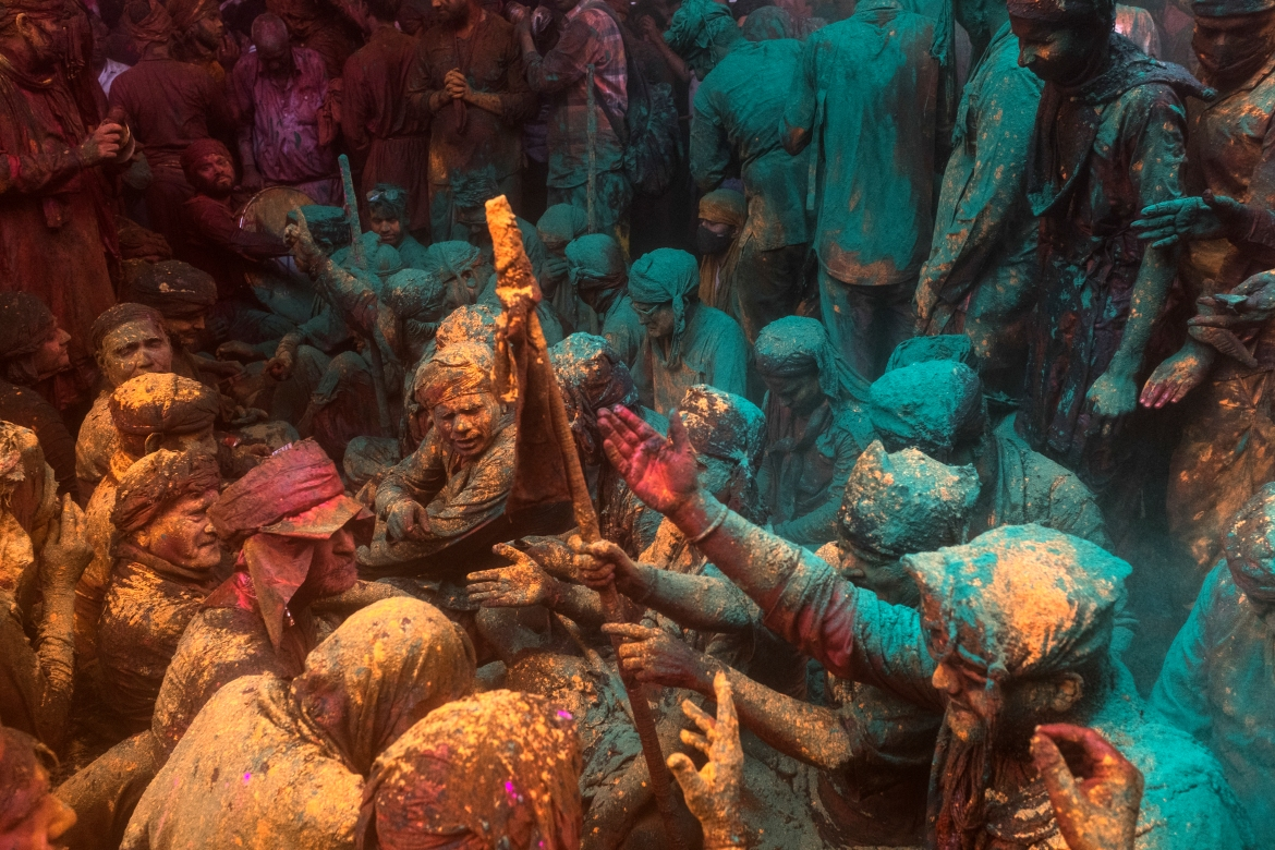 Hindu devotees take part in a traditional gathering during the Lathmar Holi celebrations. [Xavier Galiana/AFP]