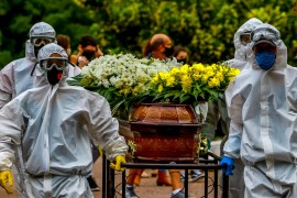 Cemetery workers carry a coffin during the burial of a victim of COVID-19 at the Sao Joao municipal cemetery in Porto Alegre, Brazil, on March 26 [File: Silvio Avila/AFP]