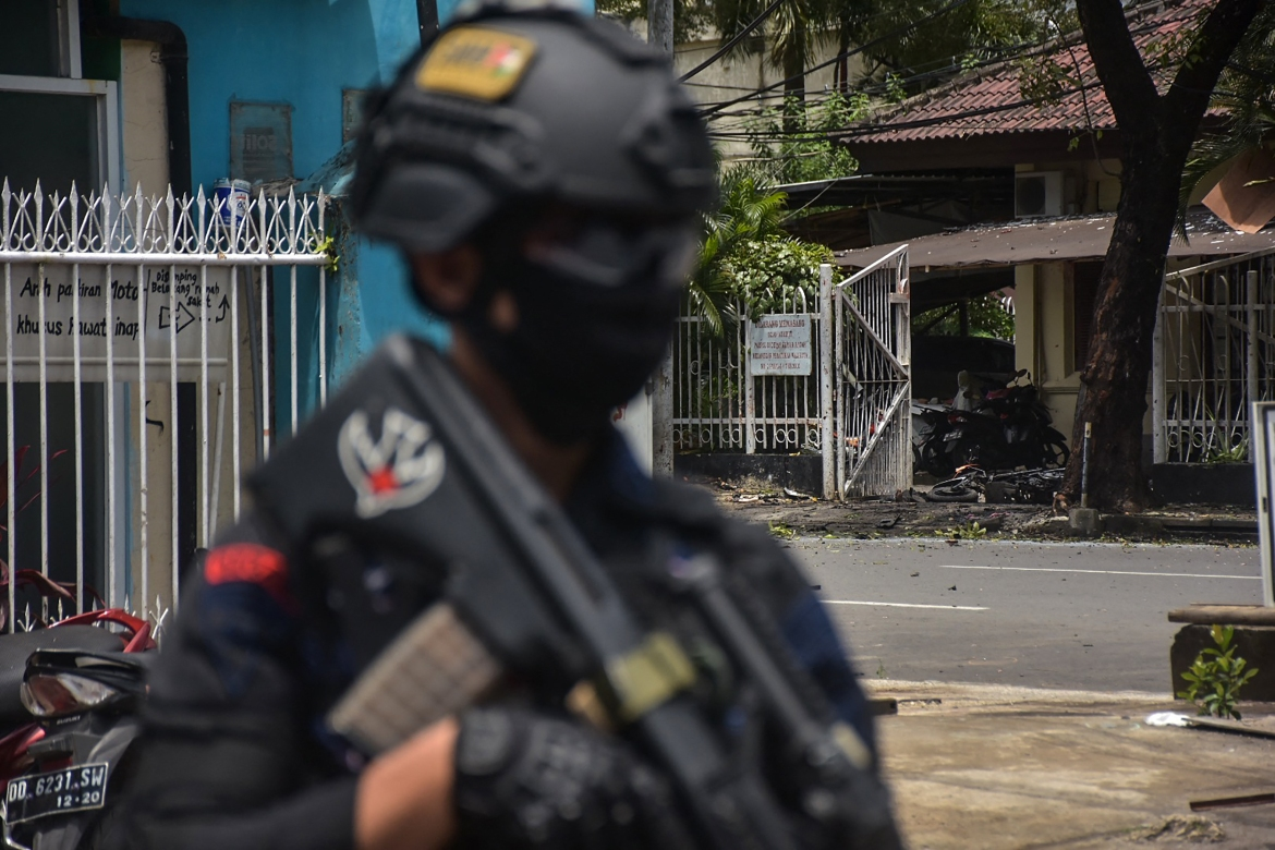 An Indonesian policeman stands guard at the site of the explosion outside the church. [Indra Abriyanto/AFP]