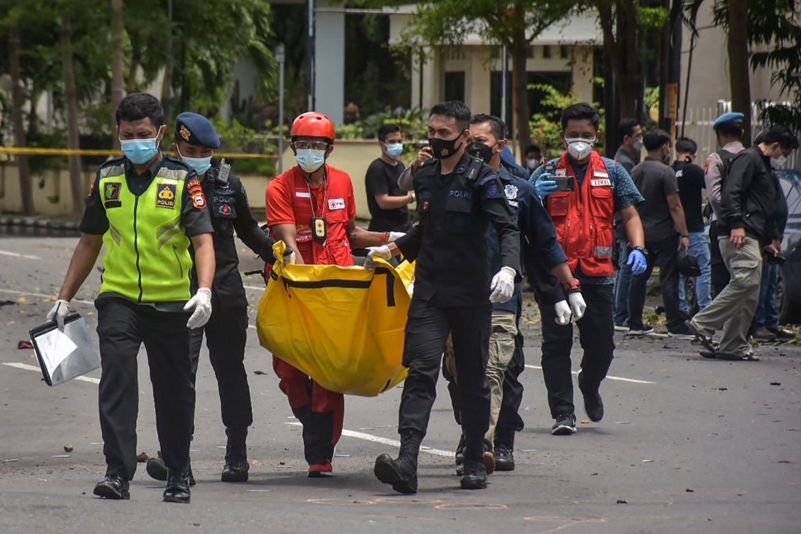 Indonesian police carry a bag with the remains of the suspected suicide bomber after the explosion. [Indra Abriyanto/AFP]