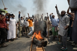 Protesters set fire to a tyre and block a road on Sunday during a nationwide strike following deadly clashes with police over Modi's visit, in Narayanganj near Dhaka [Munir Uz zaman/AFP]