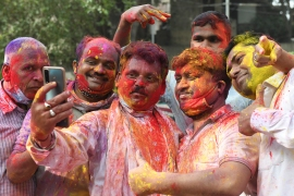 Men covered in coloured powder take a selfie as they celebrate Holi, the spring festival of colours, in Amritsar, Punjab. [Narinder Nanu/AFP]