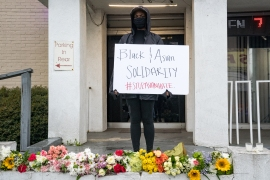 A mourner with a sign reading 'Black and Asian Solidarity #StopAsianHate' stands at the site of two shootings that occurred on March 16 at spas across the street from one another, in memorial for the lives lost, on March 17, 2021 in Atlanta, Georgia. [Megan Varner/Getty Images/AFP]