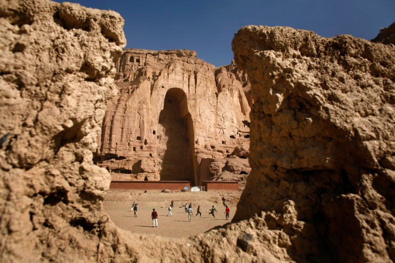Afghan boys play football in front of the gaping niche where a giant Buddha statue once stood in Bamiyan [File: Goran Tomasevic/Reuters]