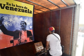 A Venezuelan exile loads boxes into a container, next to a poster of opposition leader Juan Guaido, during a collection drive of humanitarian aid in Miami, Florida, in March 2019 [File: Gaston De Cardenas/Reuters]