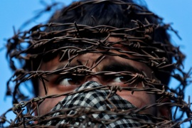 A masked Kashmiri man with his head wrapped in barbed wire during a protest in Srinagar [File: Danish Ismail/Reuters]