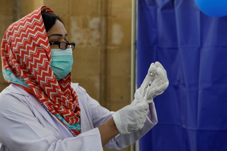 A paramedic prepares a dose of Sinopharm vaccine before administering it to a health worker at a vaccination centre in Karachi [Akhtar Soomro/Reuters]