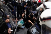 Female riot police officers surround Zaynab, daughter of human rights activist Abdulhadi al-Khawaja, during an anti-government rally demanding his release in Manama, in 2012 [File: Hamad I Mohammed/Reuters]