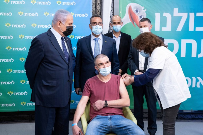 Israeli Prime Minister Benjamin Netanyahu meets the 4,000,000th person who had been vaccinated in Israel on February 16, 2021 [Alex Kolomoisky/Pool via Reuters]