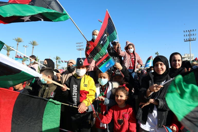 People wave Libyan flags as they gather during celebrations commemorating the 10th anniversary of the 2011 revolution in Tripoli, Libya [File: Hazem Ahmed/Reuters]